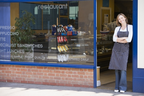 Woman Standing In Doorway Of Restaurant Smiling