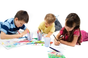 Three children brothers and their sister laying on the floor quietly entertaining themselves by drawing and coloring their favorite picture.