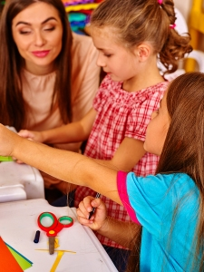 Close up of children girl with young female teacher are making something out of colored paper on table in primary school. Children craft lesson in primary school. Teacher learn children.