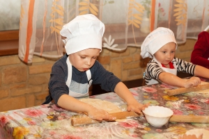 Little cook. Children make pizza. Master class for children on cooking Italian pizza. Young children learn to cook a pizza. Kids preparing homemade pizza